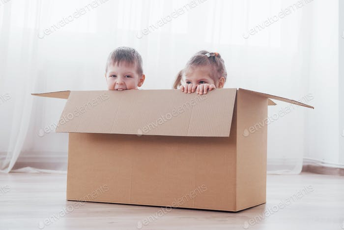 Two a little kids boy and girl just moved into a new home. Concept photo .. Children have fun