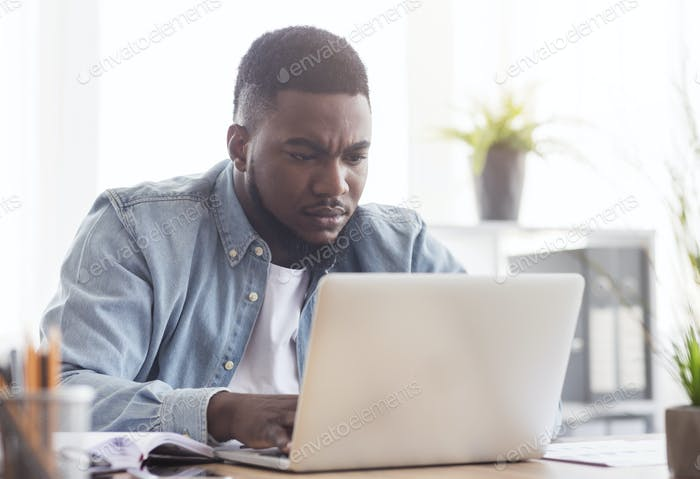 Focused african american employee working on laptop in office
