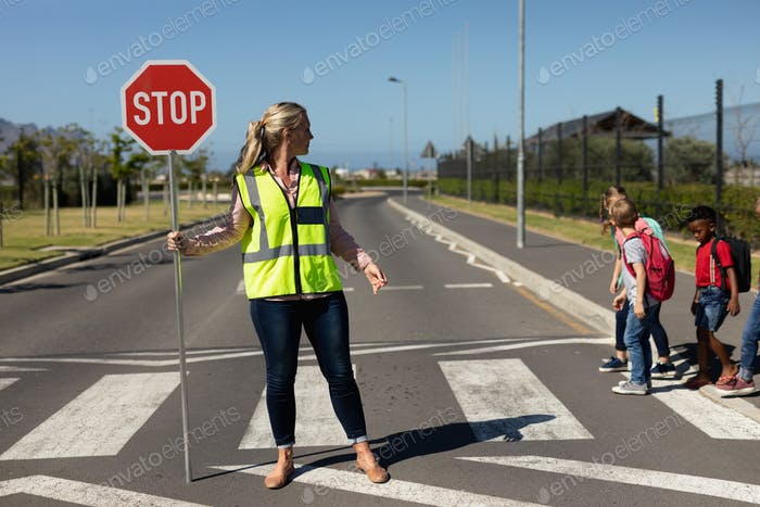 Woman wearing a high visibility vest and holding a stop sign