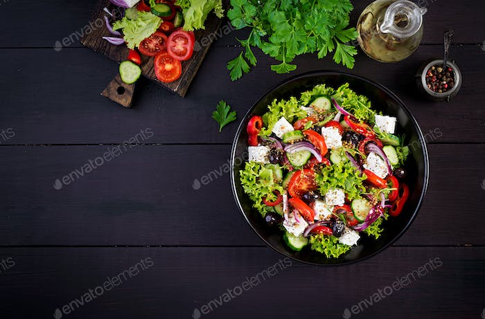 Greek salad with cucumber, tomato, sweet pepper, lettuce, red onion, feta cheese and olives.