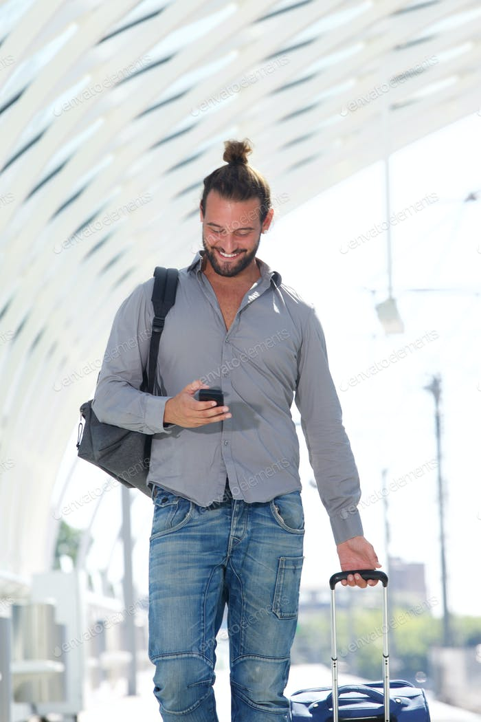 Handsome man walking with mobile phone with suitcase
