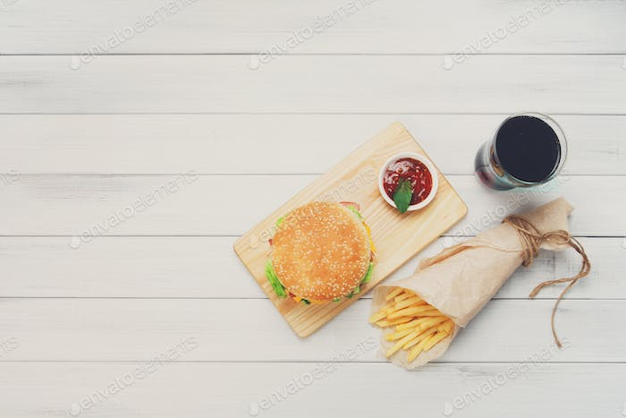 Burger, chips and cola at white wood