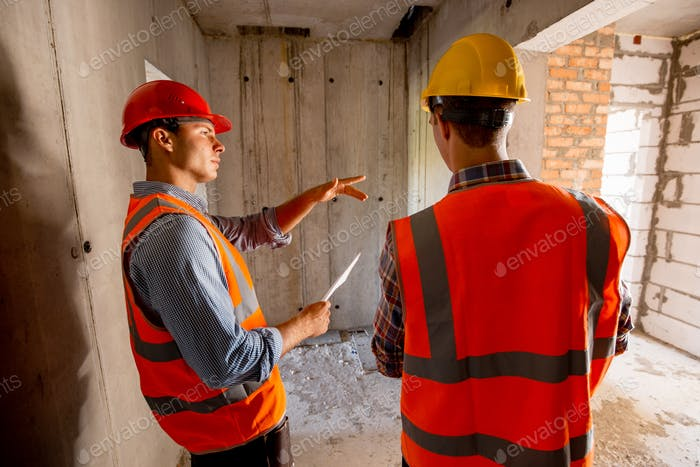 Two civil engineers dressed in orange work vests and helmets walk inside the building under