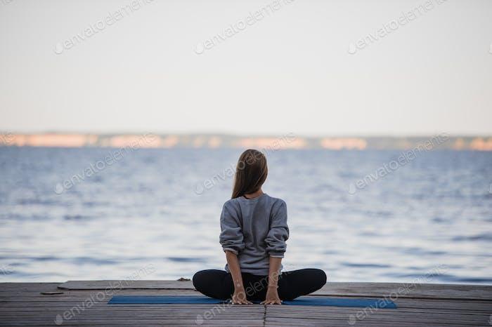 Bild von einer hübschen Frau, die Yoga am See macht