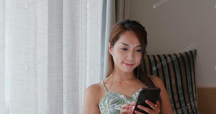 Woman look at mobile phone on bed