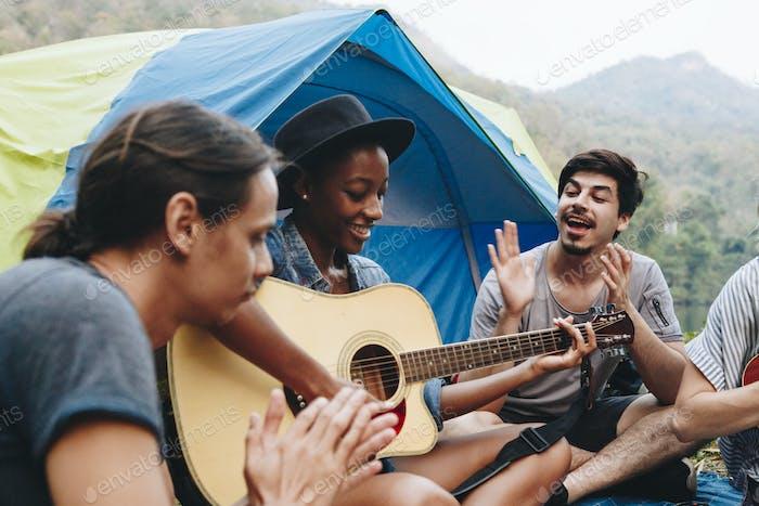 Gruppe von jungen erwachsenen Freunden auf dem Campingplatz spielen Gitarre und Ukelele zusammen singen im Freien
