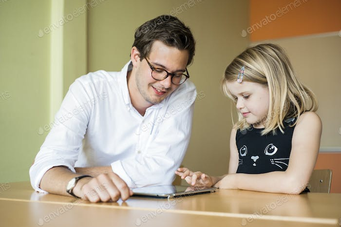 Male teacher watching girl painting on tablet computer in classroom