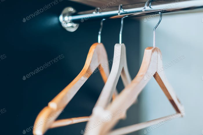 Empty Wooden hangers on rail in closet