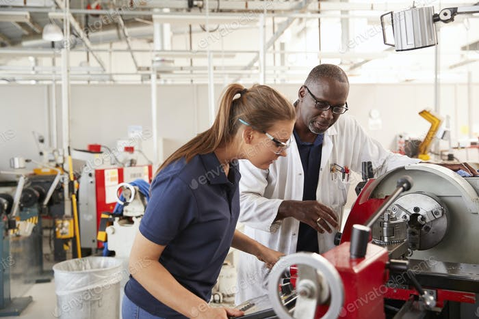 Engineer showing female apprentice how to operate machinery