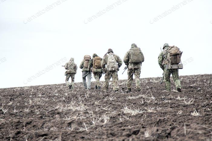 Armeesoldaten Gruppe auf Marsch im schlammigen Feld