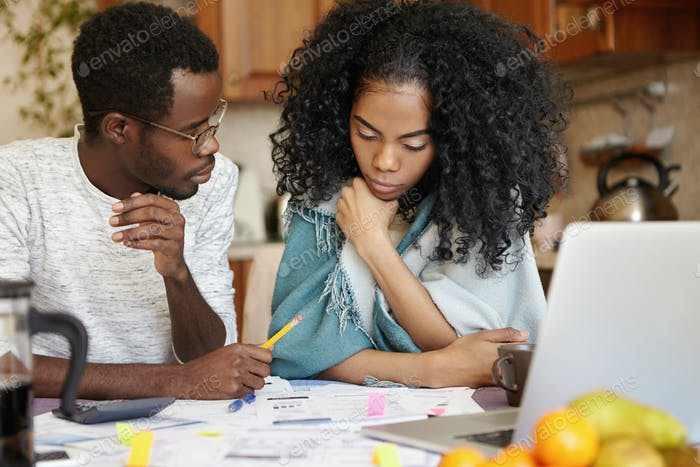 Stressed young African family of two looking desperate, sitting at table with lots of papers and lap
