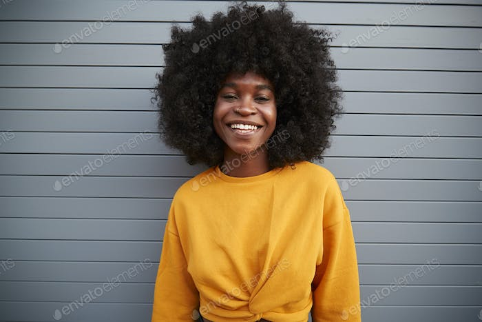 Young black woman with afro standing against grey security shutters, smiling to camera, close up