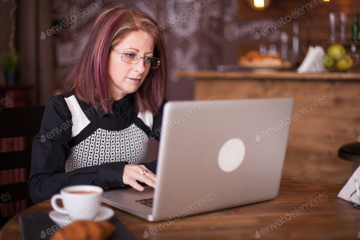 Close up portrait of adult businesswoman working on laptop