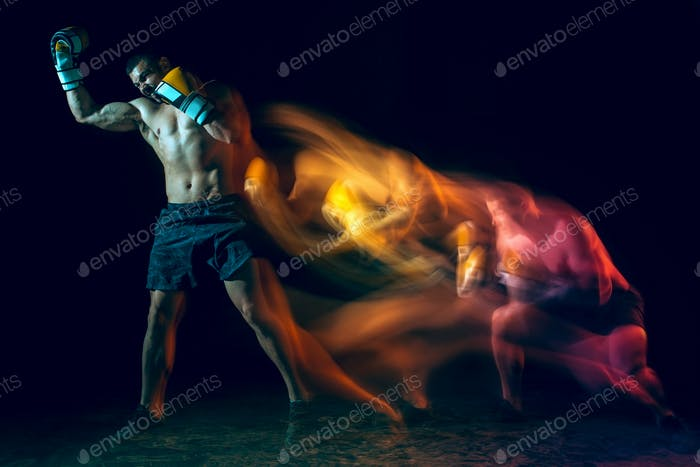 Male boxer boxing in a dark studio