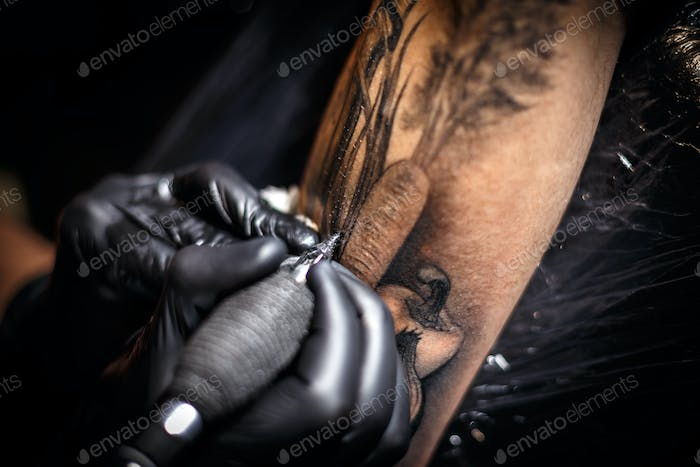 Tattoo artist creating a picture