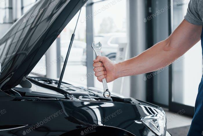 Die Hand eines Automechanikers mit einem Schraubenschlüssel in einer Kombizone in der Nähe des Autos in der Werkstatt.