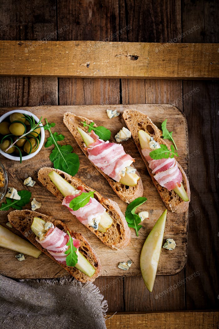 Appetizer with pear, prosciutto, ham, blue cheese for holidays and toast