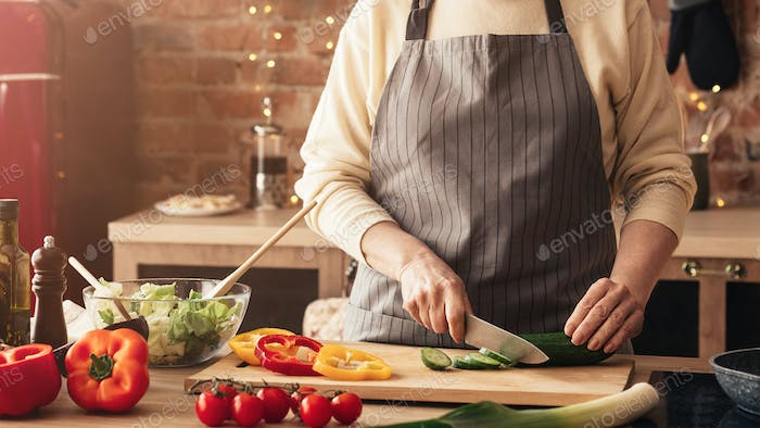 Mature woman cooking fresh vegetable salad in kitchen