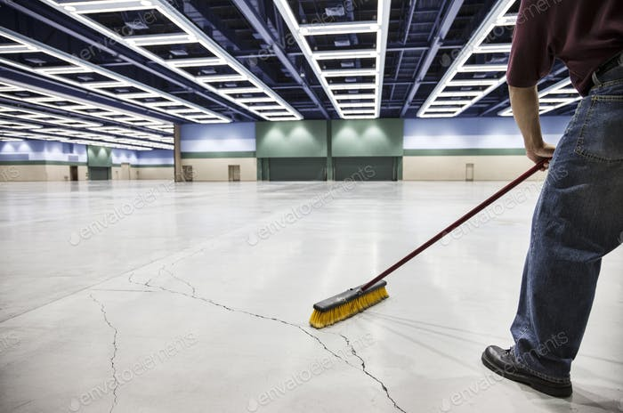 A low view closeup of a man sweeping the floor of a convention center arena.
