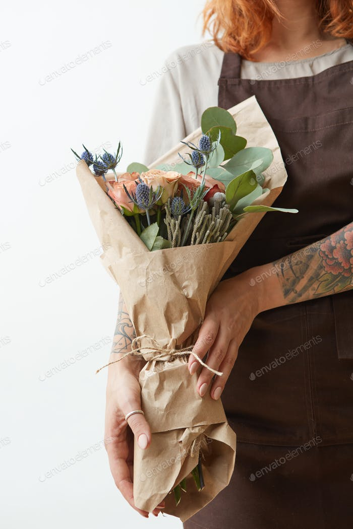 Female in a brown apron with red hair hold nice bouquet from living coral colored roses and eryngium
