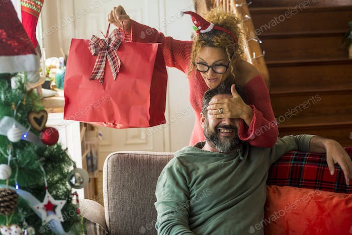 Cheerful wife adult woman give christmas holiday gits to her husband man - cheerful and happy
