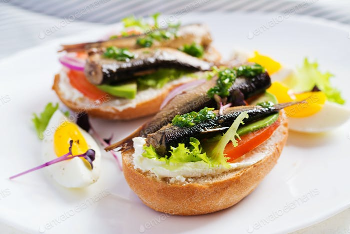 Sandwich - smorrebrod with sprats, avocado, tomatoes, eggs and cream cheese