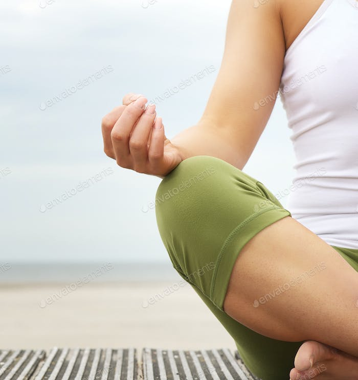 Young woman in lotus position with yoga hands