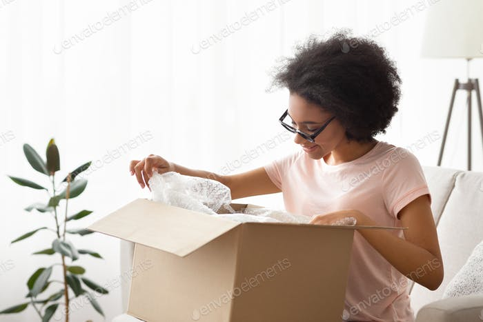Girl in glasses unpacks purchase and considers it