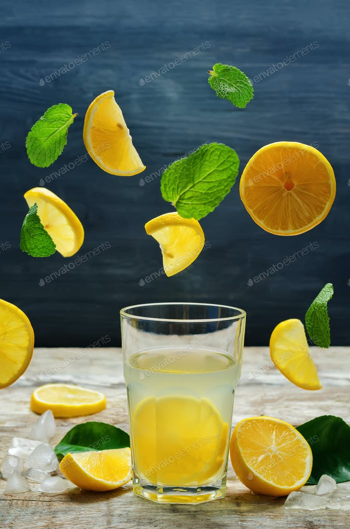 Lemonade with flying lemon, mint and ice
