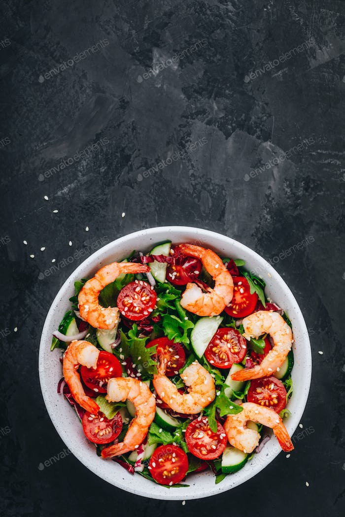 Shrimp salad with fresh green lettuce and radicchio leaves, cucumbers, tomatoes and sesame seeds.