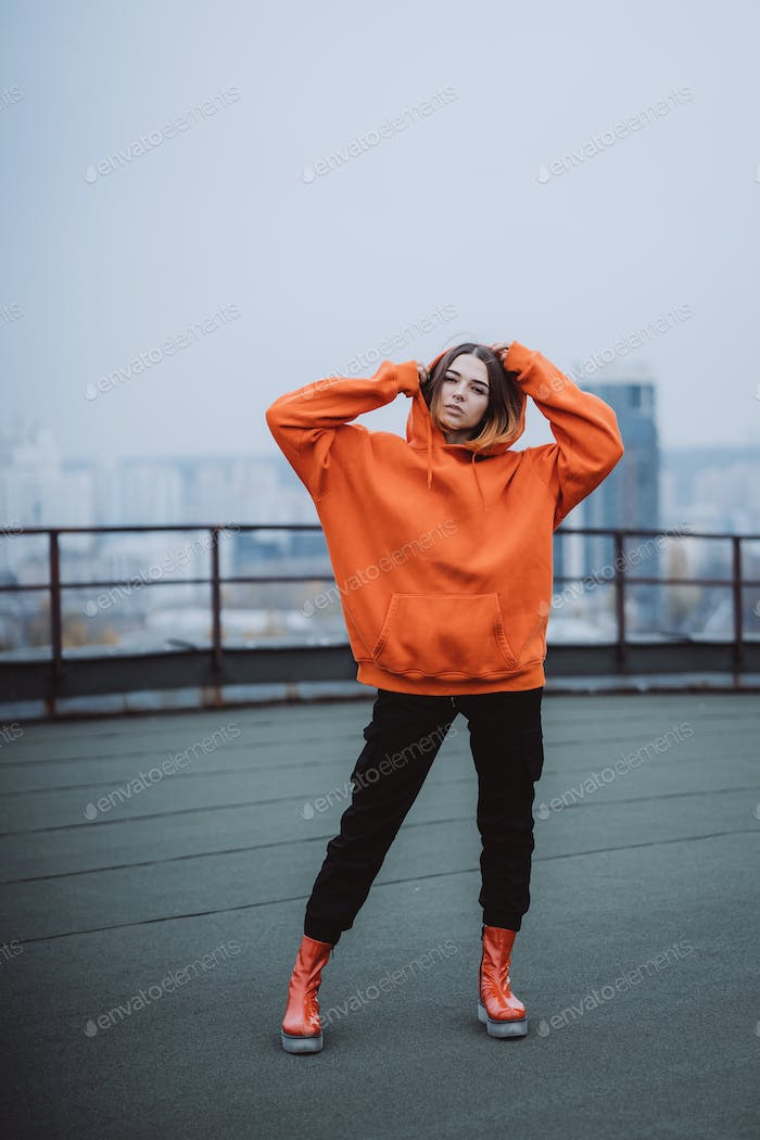 Girl in an orange jacket poses on the roof of a building in the city center