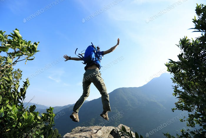 Fearless hiker jumping on the cliff edge on mountain top