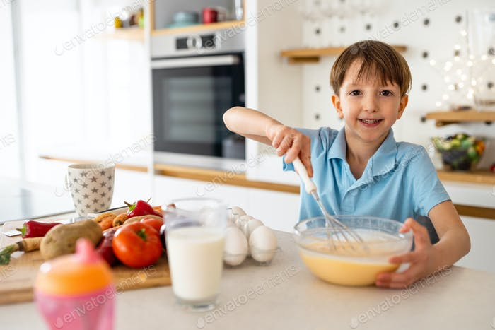 Happy child prepare food and having fun in kitchen. Healthy eating