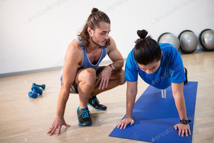 Instructeur de fitness aidant l'homme de fitness avec push-up
