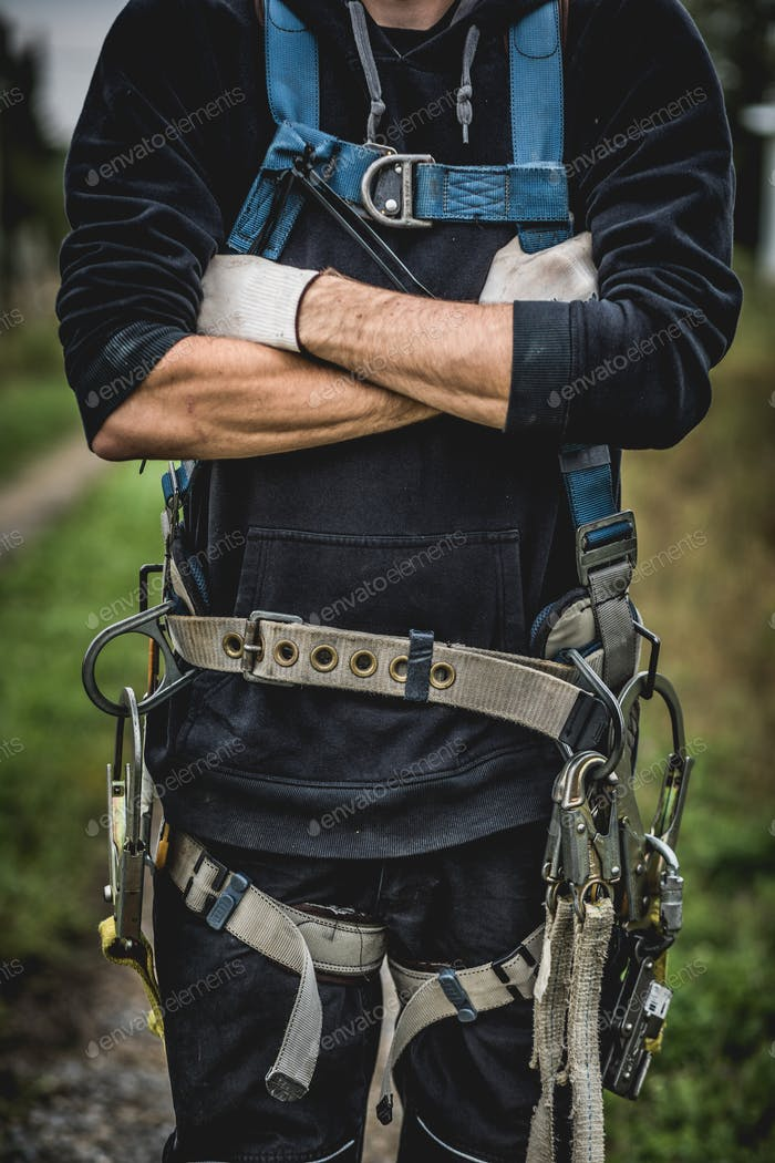 Technician in uniform with harness standing with arms crossed.