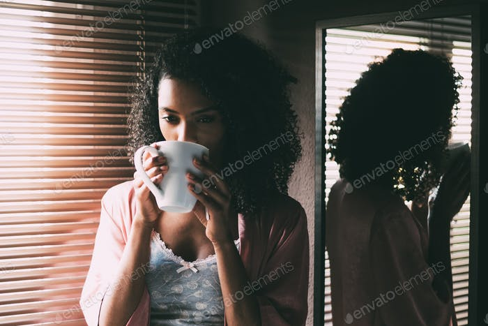 pretty black woman standing at the window with cup of coffee