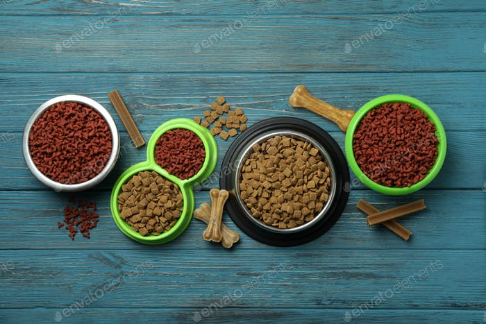Bowls with pet feed on wooden background