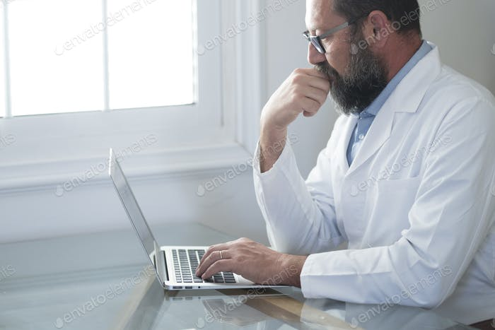 Adult mature Caucasian male doctor in white medical uniform sit at desk in office consult online
