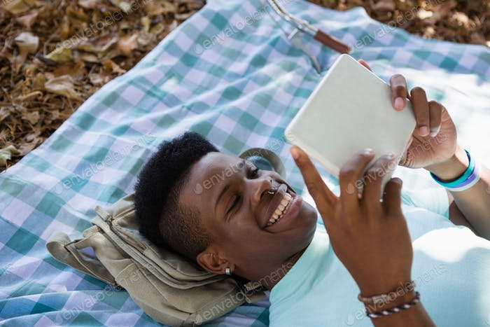 Man using digital while lying on a picnic blanket
