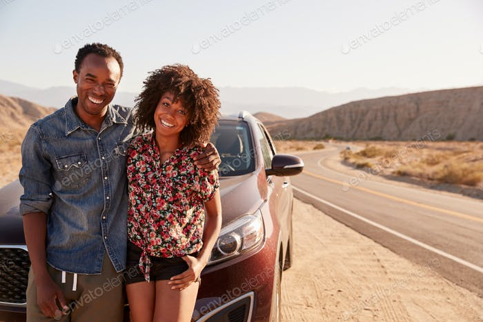 Young black couple standing on desert roadside by their car