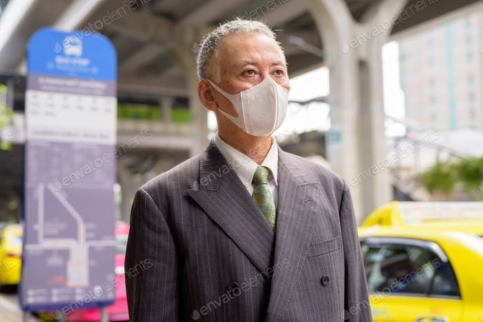 Mature Japanese businessman with mask thinking at the bus stop