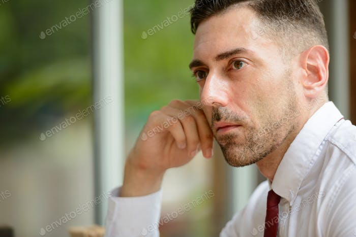 Face of handsome businessman thinking at the coffee shop