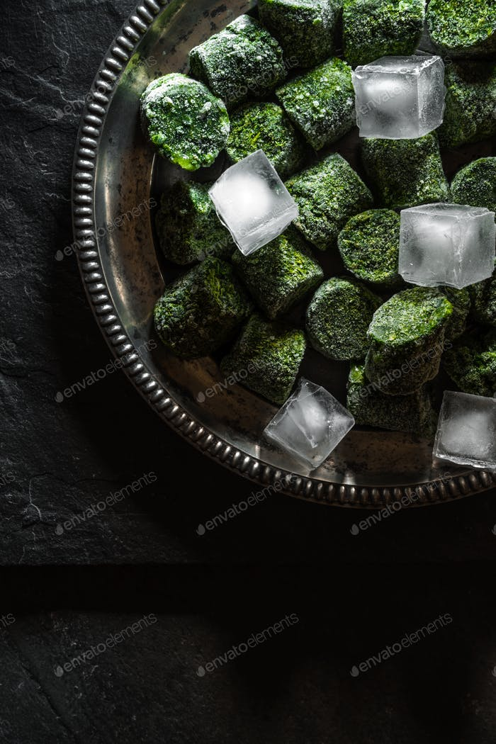 Frozen spinach in briquettes and ice on a tin plate