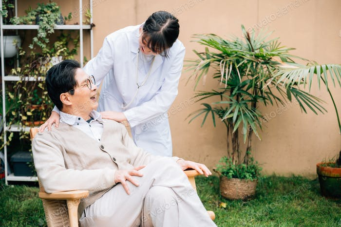 Senior Mann mit jungen Ärztin auf dem Hof