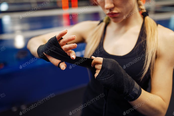 Woman winds up black bandages, boxing training