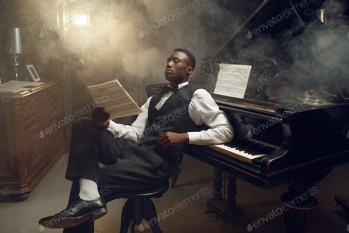 Ebony pianist with music notebook, jazz musician
