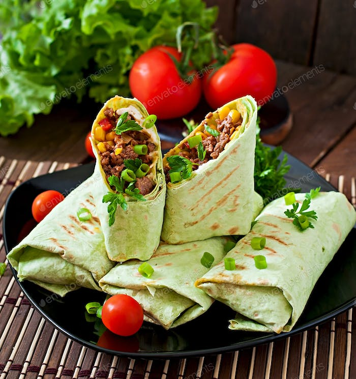 Burritos wraps with minced beef and vegetables on a wooden background