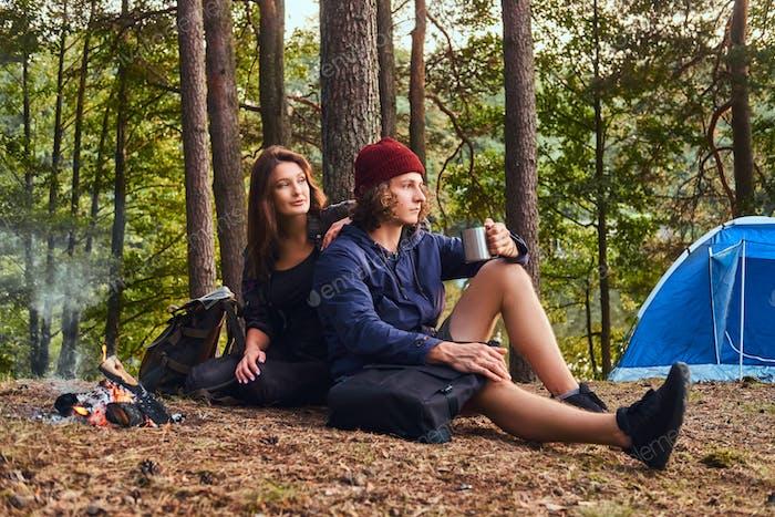 Junges Hipsterpaar wandern im Wald wärmend in der Nähe eines Lagerfeuers im Lager.