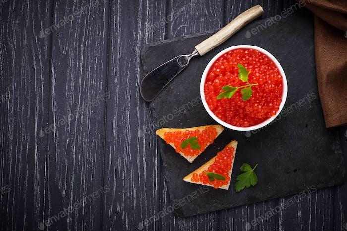Red caviar on slate background