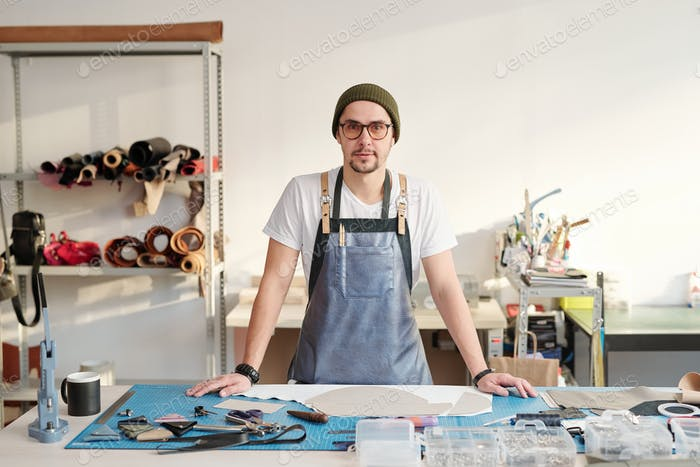 Young creative master in apron and beanie hat standing by table in workshop